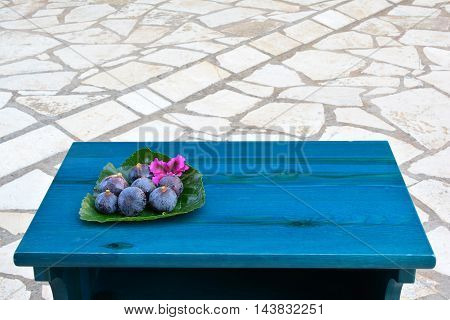 Sevenl ripe blue figs with pink flower served on big mulberry leaf on blue wooden table in a yard paved with marble side view