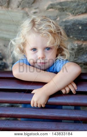 Little child three year old with blond curly hair hidden behind a wooden bench