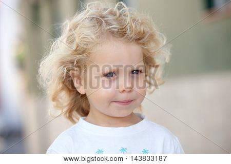 Beautiful boy three year old with long blond hair on a sunny day