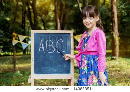 funny little girl teaches alphabet. The concept of learning and school