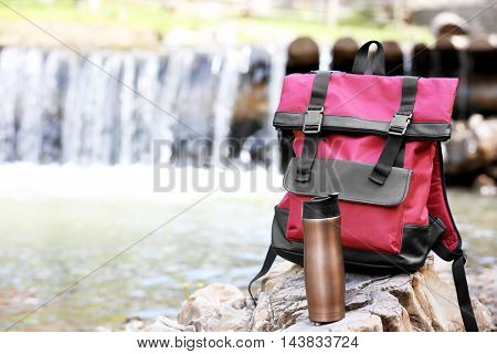Backpack and bottle on stone on waterfall background