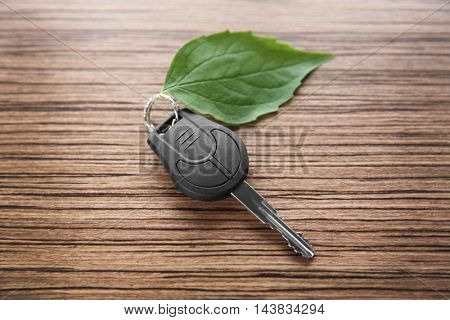 Car key with green leaf on wooden table