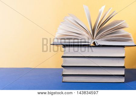 Open book, hardback books on wooden table. Education background. Back to school. Copy space for text.