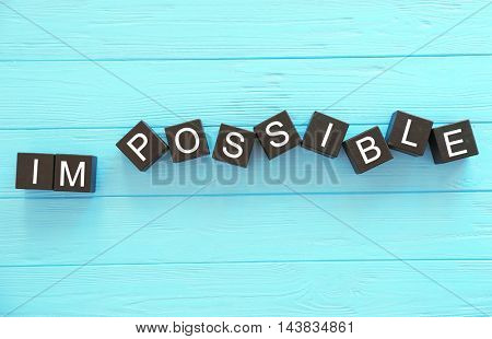 Black cubes with word IMPOSSIBLE on wooden background