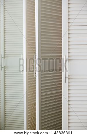 White louvre door of dressing cabinet with handle
