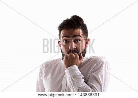 Picture of frightened handsome man looking at camera while posing for photographer isolated on white background in studio.
