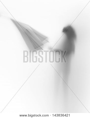 Diffuse body slihouette of a young girl with umbrella