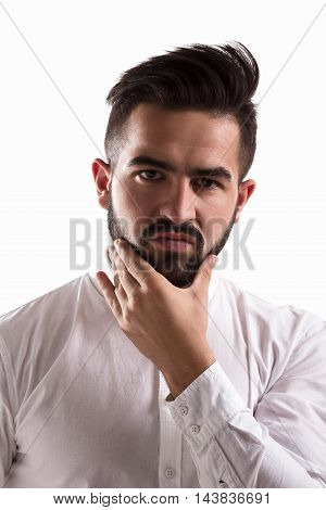 Portrait of doubtful handsome man looking at camera and touching his beard. Young hipster man posing for photographer isolated on white background.