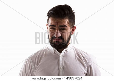 Image of hatred handsome man looking at camera. Bearded hipster man posing for photographer isolated on white background in studio.