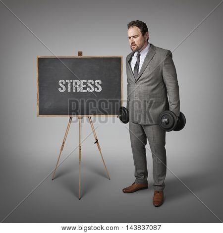 Stress text on blackboard with businesssman holding weights