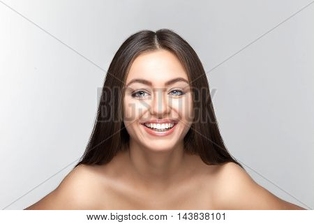Portrait of attractive caucasian smiling woman brunette on gray background, studio shot toothy smile face long hair head and shoulders
