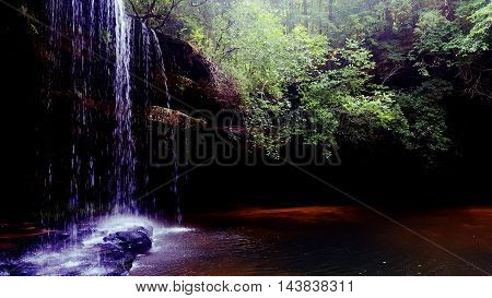 Waterfall with a shallow pool and cave behind it
