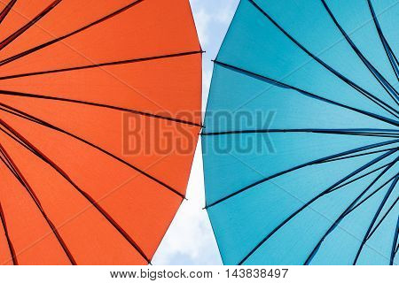 Two bright umbrella located next to each other against the sky