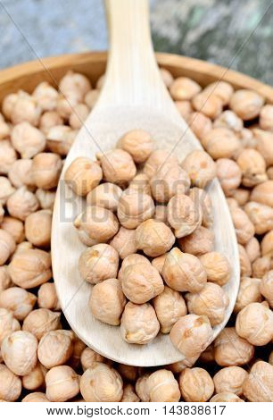 Bowl and spoon with chickpeas on table