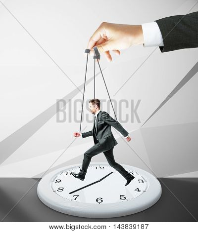 Huge hand making businessman run on abstract clock. Abstract concrete background. Manipulation and control concept