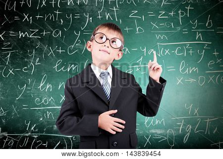 Little schoolboy on chalkboard background