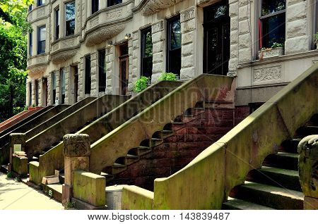 New York City - August 10 2013: Typical townhouses with stoops and stairways on West 162nd Street in the Morris-Jumel Historic District