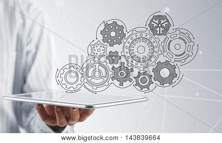 Close view of businessman showing tablet pc with gears on screen