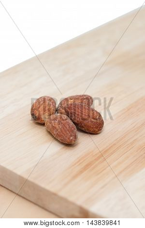 Almonds on a wooden cutting board background.
