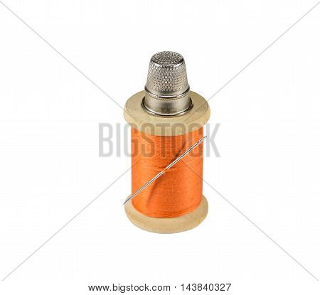 Spool of thread needle and thimble on white