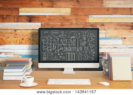 Closeup of creative workplace with business sketch on computer screen colorful book keypad coffee cup and other items on aged wooden background
