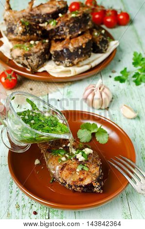 Steaks of carp in bread crumbs and spices with fish broth. Fish cooked on the grill