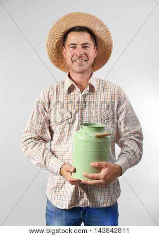 Milkman with watering can on light background