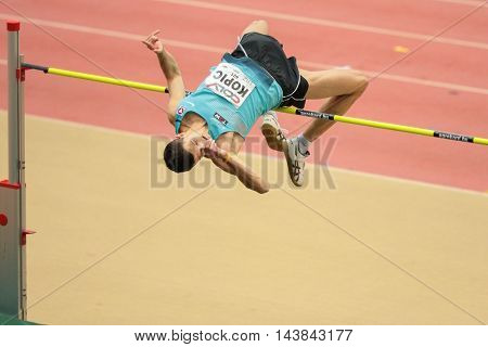 LINZ, AUSTRIA - FEBRUARY 6, 2015: Josip Kopic (#401 Austria) competes in the men's high jump event in an indoor track and field event.