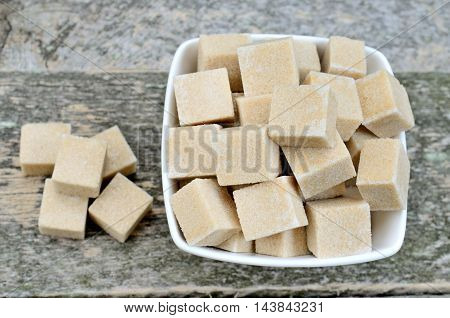 Beige sugar cubes in a ceramic bowl on wooden table