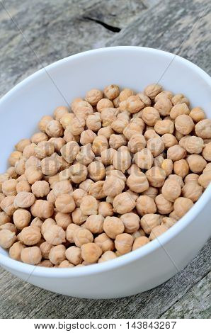 Chickpeas in a ceramic bowl on wooden background