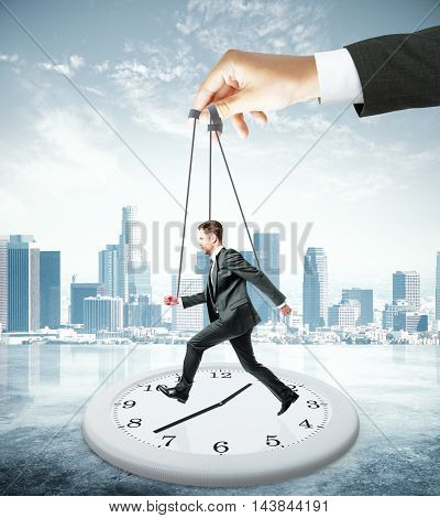 Huge hand making employee run on abstract clock. City background. Manipulation and control concept