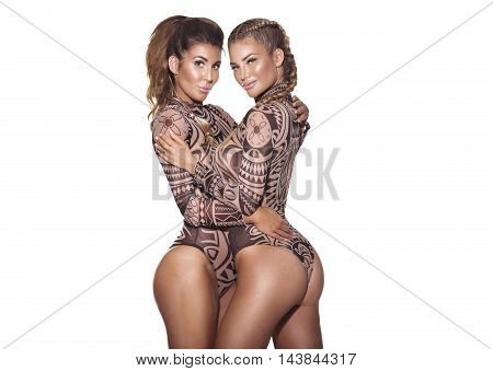 Two beautiful sexy girls posing in studio looking at camera. White background.