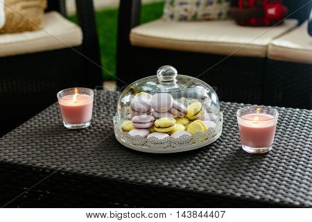 Colorful macaron on a plate under a glass cover. Put on a beautiful table surrounded by candles.