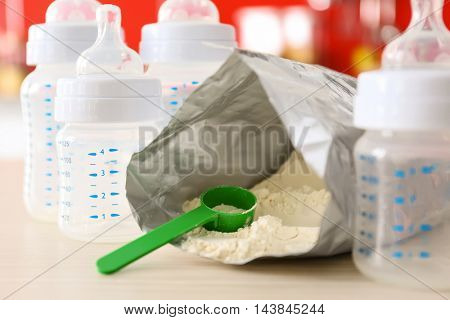 Feeding bottles and baby milk formula on kitchen background