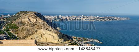 Panoramic view on Alicante harbor with high mountain and spit going to the sea, summer Spain