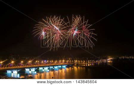 Fireworks over the city in a large river with a bridge in lights
