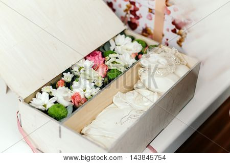 Wooden box with gifts for a newborn. Inside the suit, booties and flowers.