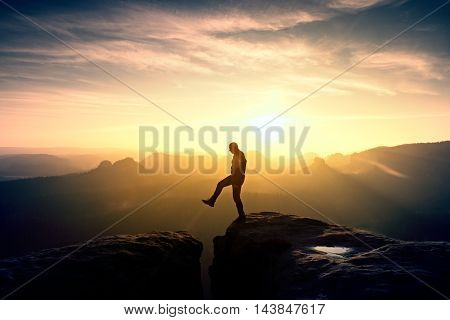 Silhouette Of Jumping Man And Beautiful Sunset Sky. Vintage Effect