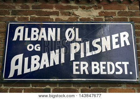 VEJLE DENMARK - AUGUST 22 2016: Danish vintage metal Albani Beer signboard at a wall with old bricks on August 22 2016