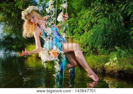Girl on home made tree swing over river. Swing decorated with flowers. Woman with flower wreath on head.