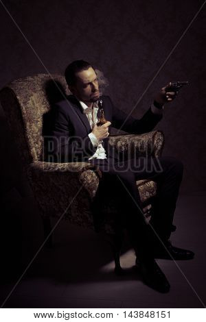 Young handsome and elegant man sitting in chair, holding gun and smoking a pipe isolated over vintage background