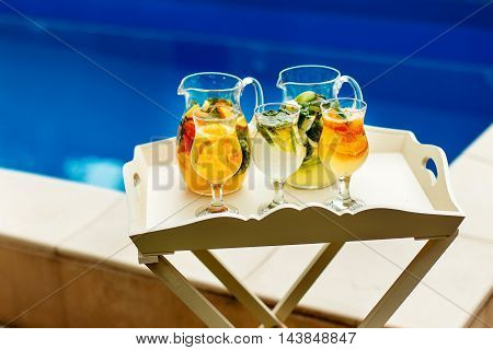 Delicious cocktail in jugs on the background of the pool. Put on the beautiful table.