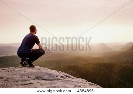 Tourist In Squatting Position On Peak Of Sandstone Rock And Watching Into  Valley