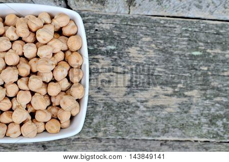 Bowl with chickpeas on  rustic wooden table