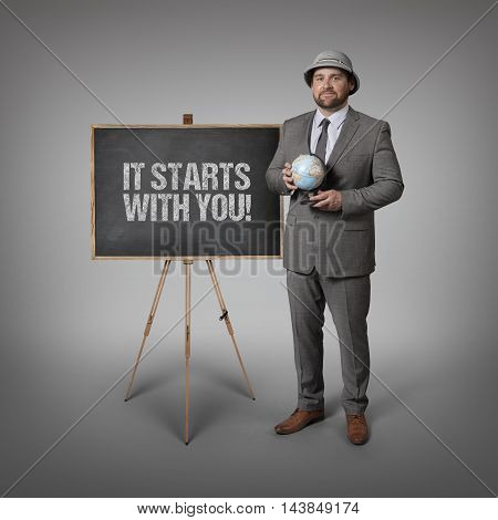 It starts with you text on blackboard with businessman holding globe in hands