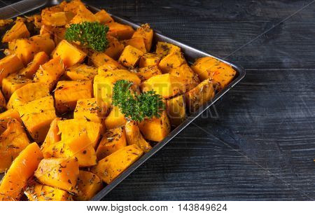 Baked pumpkin slices with spices and oil