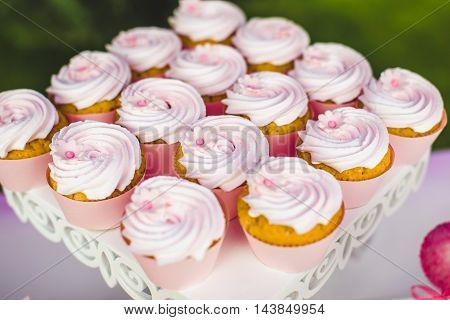 Gourmet cupcakes with white buttercream frosting on white wooden table