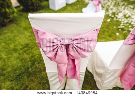 Wedding chair with pink bow on the grass