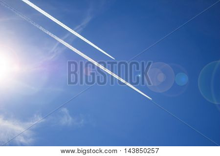 Two planes flying in parallel leaving a white trail a bright Sunny day