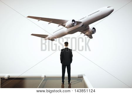 Travel concept with businessman on roof looking at flying by airplane. Grey sky background